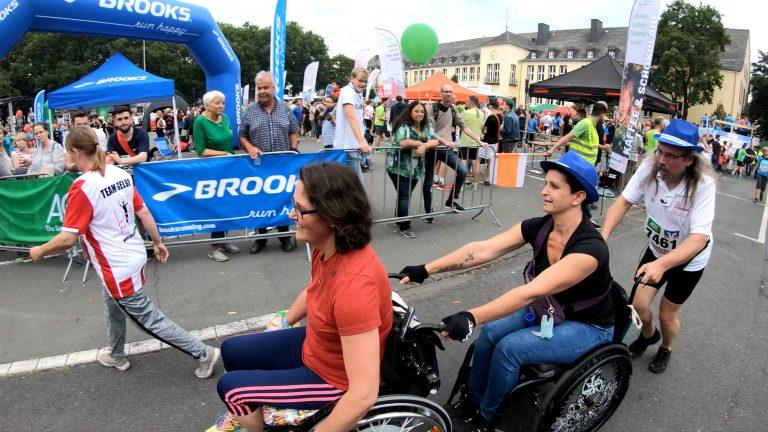 Ein Mann mit Hut und Bart schiebt eine Frau im Rollstuhl. Diese schiebt schiebt vor sich ebenfalls einen Rollstuhl.